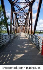 Long view down former train bridge now walking bridge over St John River in Fredericton, New Brunswick Canada