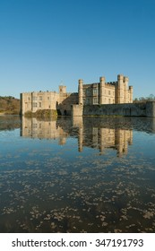 Long view of Leeds Castle with moat in foreground.