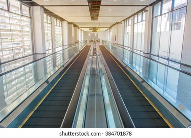 long walkway of escalator at international airport terminal.