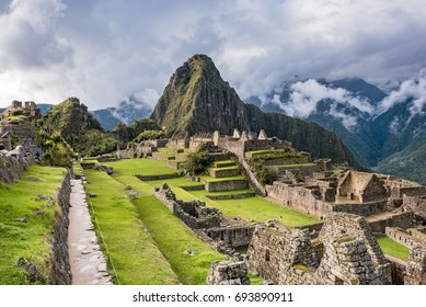 Long walkway into Machu Picchu above the ruins on the west side with afternoon sunshine