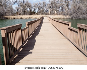 A long walkway, made of composite material, spans over water.