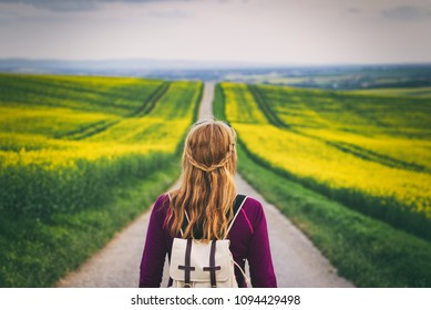 Long way to go. Woman travelling in countryside. Tourist standing on the road. Travel concept. Challenge of journey