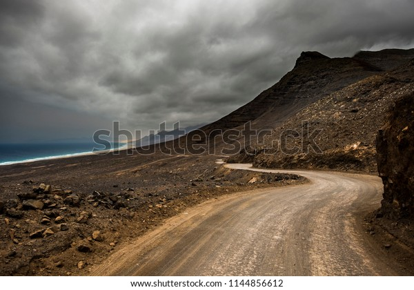 long way road no asphalt to go to a wild beach and mountains. offroad path for alternative detination. enjoying the discover of new places. adventure and travel concept