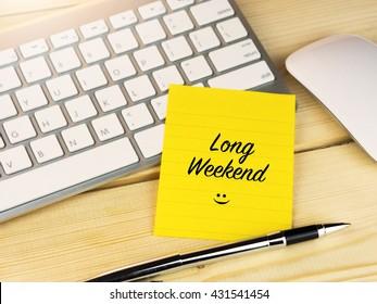 Long weekend on sticky note on work desk