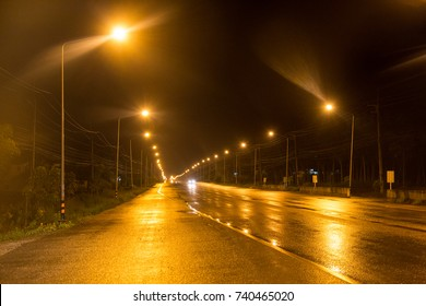 long wet road after rain and street light at night time