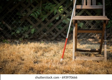 Long White Cane for the Blind Resting on an Empty Wooden Chair  (Copy Space)