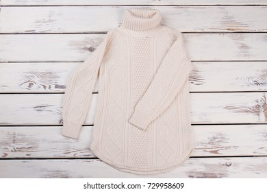 Long white knitted sweater with roll neck. Stylish woolen pullover. Fashionable handmade item of women's wardrobe.