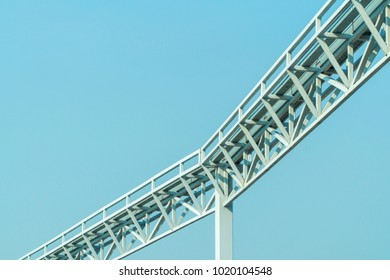 Long white steel frame with blue sky.