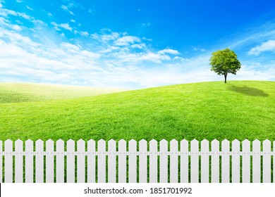 Long white wooden fence with Green grass meadow field and little hill with white clouds and blue sky in background.