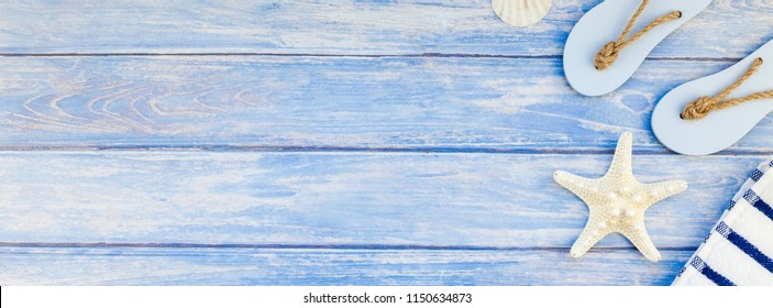 Long wide banner flat lay concept summer travel vacations. Top view of towel flip flops seashells and starfish pastel blue wooden planks background with copy space in rustic style frame template text