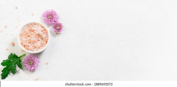 Long wide banner with fresh organic Himalaya salt in a bowl with aromatic purple flowers and green leaves on white marble background. Spa and wellness banner concept.