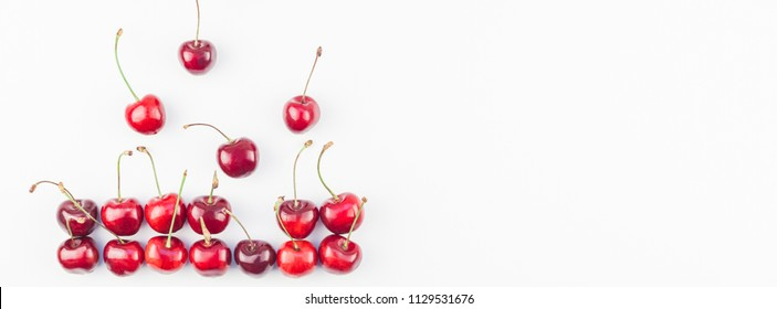 Long wide banner of fresh ripe cherry pattern layout with copy space isolated on white background in minimal style. Concept of summer fun and healthy eating. Template for your text or food design