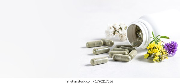 Long wide banner with natural herbal pills for detox and immunity support in pandemic time. Big herbal pills in white plastic bottle on white background with copy space for your text.