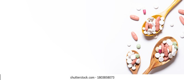 Long wide banner with three wooden spoons with assortment of different medical capsules. tablets and pills on white background top view. Flu season concept. Health care concept.