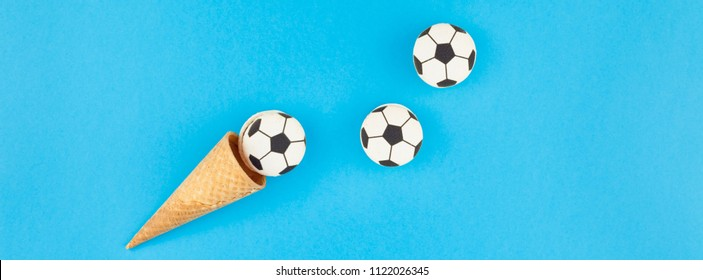 Long wide banner top view of ice cream waffle cones with soccer balls macarons on bright bold blue background with copy space in minimal style, concept of football games for children birthday