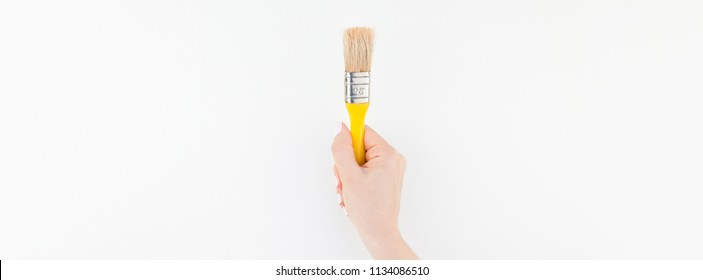 Long wide banner of woman hand holding new paint brush with copy space isolated on white background in minimalism style. Template for feminine blog, social media. Repair or improvement concept