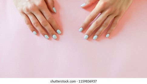 Long wide banner of woman hands with bright blue nails over pink background, minimal style. Concept template feminime blog, beauty concept, care