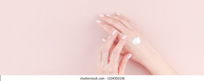 Long wide banner of woman moisturizing her hand with cosmetic cream lotion with copy space on millennial pink background minimalism style. Concept template feminine blog, social media, beauty concept