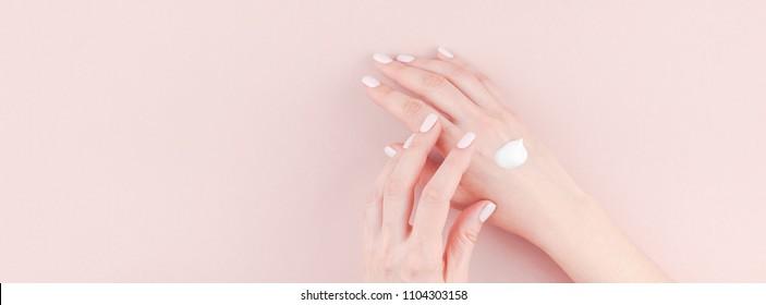 Lange breite Banner der Frau Feuchtigkeit ihre Hand mit Kosmetikcreme Lotion mit Kopienraum auf Jahrtausend rosa Hintergrund Minimalismus Stil. Concept Template feminine Blog, Social Media, Beauty Concept