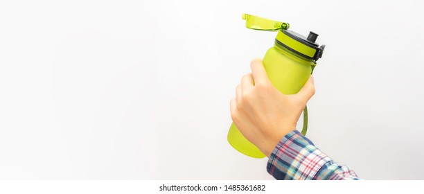 Long wide banner with woman preparing to drink water from  green plastic free reusable bottle  on white background with copy space. Ecology protection concept. BPA free materials Zero waste concept