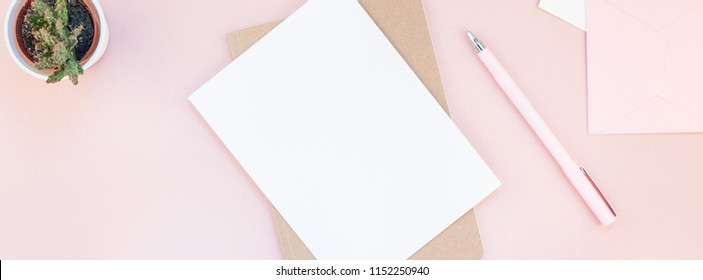 Long wide banner of workspace desk styled design office supplies and cactuses succulents with copy space millennial pink color paper background minimal style. Template for feminine blog social media