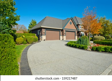 Long and wide nicely paved driveway to two double doors garage in the suburbs of Vancouver, Canada.