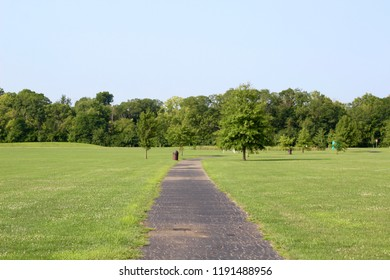 The long winding blacktop sidewalk in the park on a sunny summertime day.