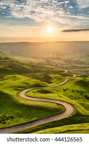A long and winding road passing through green hills at sunset.