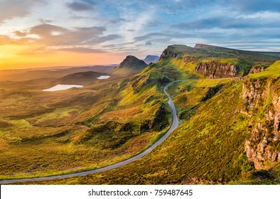 Long winding road at Quiraing on the Isle of Skye with a beautiful vibrant sunrise sky.