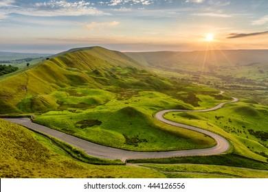 Long and winding rural road leading through green hills in the Peak District, UK at sunset.
