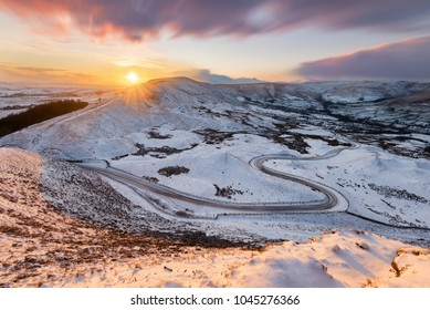 Long winding rural road in the Peak District with snow and beautiful sunset.
