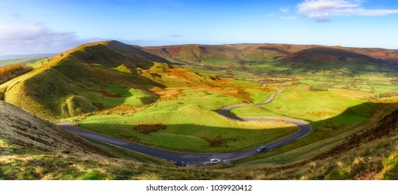 Long and winding rural road of Winnat Pass  leading through green hills in the Peak District, UK