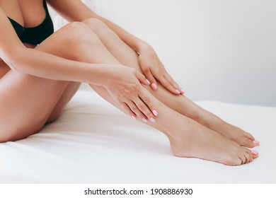 Long woman legs after procedure of epilation on light background. Girl stroking her feet. The concept of epilation, waxing, shugaring, skin care, manicure and pedicure