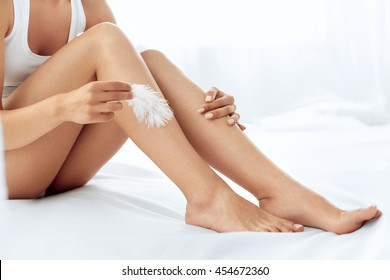 Long Woman Legs With Beautiful Smooth Skin. Closeup Of Female Hand Touching Perfect Hairless Soft And Silky Skin With White Feather. Hair Removal And Epilation, Beauty Body Care Concepts