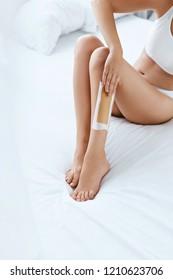 Long Woman Legs With Hair Wax Strip Closeup. Hair Removal