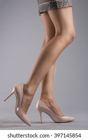Long woman legs on grey background