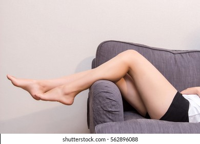 Long woman legs on sofa.