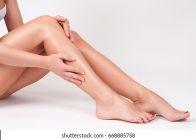 Long woman legs with smooth skin after depilation. Female hand touching perfect hairless soft and silky skin. Hair removal and epilation