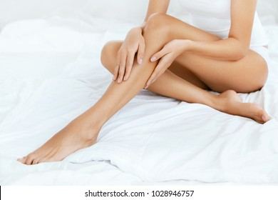 Long Woman Legs With Smooth Soft Skin. Close Up Of Female With Perfect Healthy Silky Legs Skin After Hair Removal On White Bed In Light Interior. Beauty, Skin Care Concept. High Resolution.