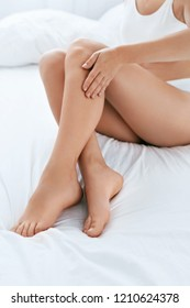 Long Woman Legs With Smooth Soft Skin On White Bed Closeup