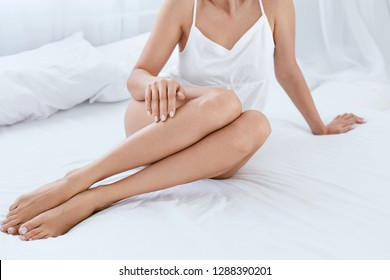 Long Woman Legs With Smooth Soft Skin Without Hair On White Bed