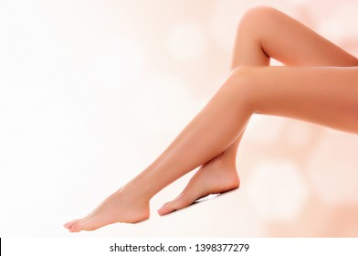 Long woman naked legs with smooth and clear skin. Laser hair removal concept. Abstract background with blurred lights