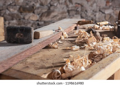 Long wood plank sitting on table next to assorted carpenter tools with blurred stone wall in background