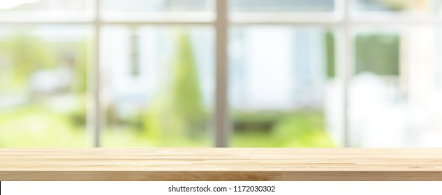 Long wood table top with blur banner background of green garden outside the window, for montage or display your products