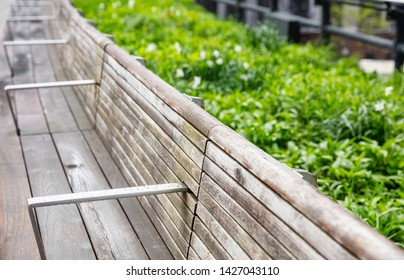 Long wooden bench with steel handles, empty after the rain, blur green grass background, Manhattan New York downtown