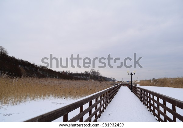 A long wooden boardwalk on the lake in winter