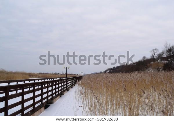 A long wooden boardwalk on the lake in winter