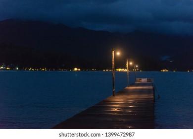 Long wooden bridge with light in beautiful tropical island beach at dark blue sky