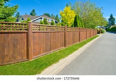 Long wooden cedar fence on the empty street.