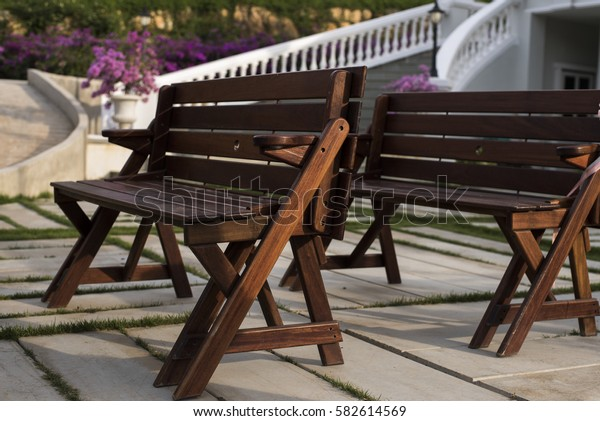 Long wooden chairs in the park